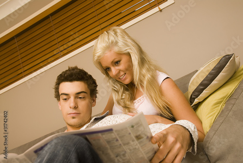 Young couple looking at classifieds in the newspaper