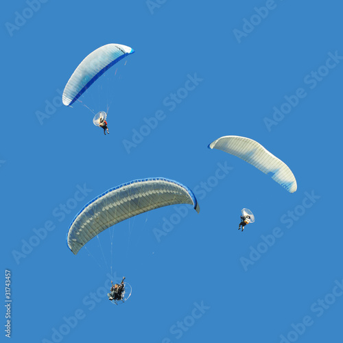 White blue paramotor on blue sky