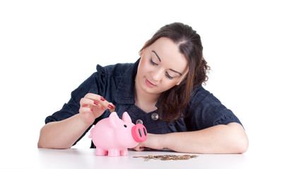 thoughtful fat young woman with pink piggy bank