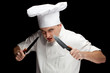 angry male cook in uniform with two knifes, black bckground..