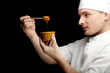 male cook in white uniform with bowlof honey, black bckground.