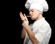 smoking young male cook in white uniform, black bckground.