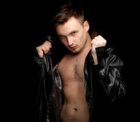 serious young man in leather jacket, black background