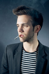 Cool young man smoking a cigarette