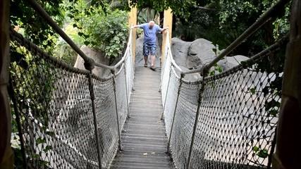 Mann auf Hängebrücke