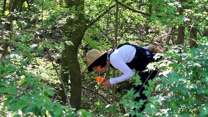 Eine Frau riecht intensiv an einer Tulpe im Wald
