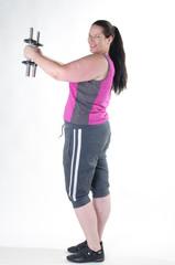 Übergewichtige Frau macht Hanteltraining mit Spaß