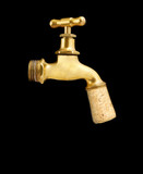 Old gold faucet closed with cork isolated on black