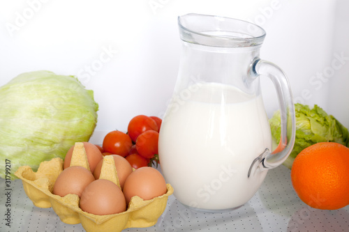 refrigerator with some kinds of food - vegetables, milk, eggs