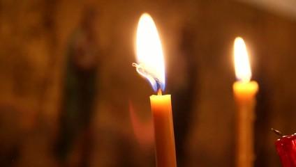 Горящие свечи на фоне иконы