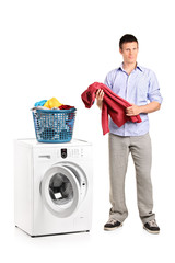 Full length portrait of a man holding a blouse and a washing mac