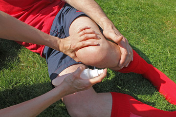 Therapist attending to injured sportsman
