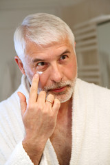 Portrait of senior man applying moisturizing cream