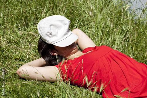 jeune femme au repos couchée dans l'herbe