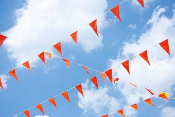Orange hanging festive Dutch Flags against a blue sky