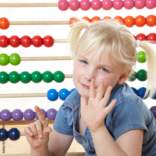 Cute blond child using an abacus to count