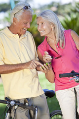 Happy Senior Couple Cycling Using GPS on Smart Phone