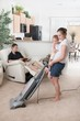 A Mother Trying To Vacuum While The Father Sits Around