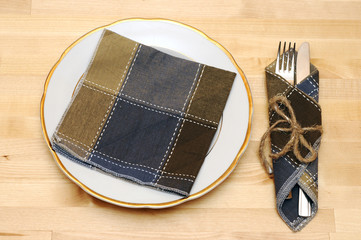 knife and fork in textile napkin on wooden table