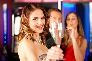 Drei Freunde mit Sekt in Bar oder Casino