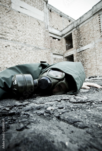 Man with gas mask fallen on the ground