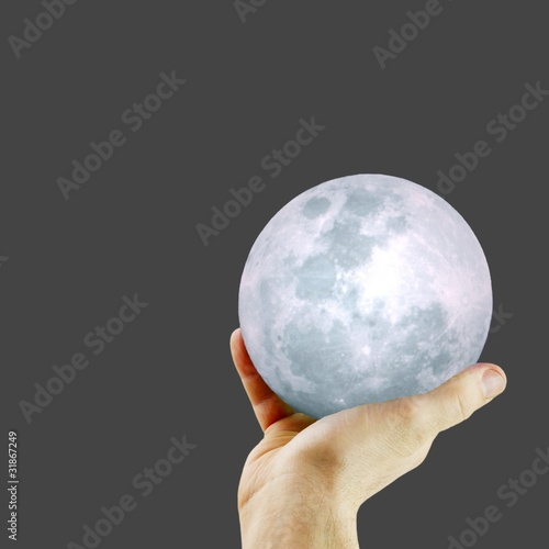 A hand with a softly glowing moon against a black background