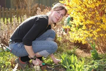 Eine glückliche junge Frau arbeitet im Garten