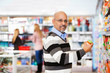 Smiling mature man shopping in the supermarket