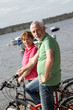 Senior couple on bicycle ride by a lakeside