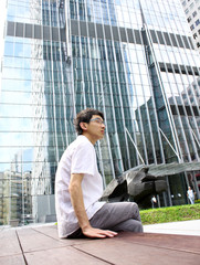 businessman sitting on a bench in front of an office building