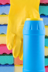 Yellow rubber glove and bottle of a cleaner