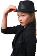 Beautiful young woman holds her hat bolder.