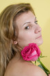 Beautiful young girl with pink rose on yellow background