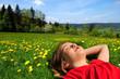 Mädchen liegt auf Blumenwiese