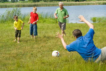 family playing soccer on the grass
