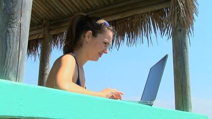 Young woman at tropical cabana on laptop