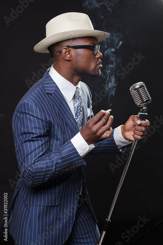 Black man with blue striped suit and white hat singing.