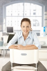 Young woman sitting in office smiling