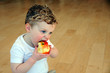 Young boy takes bite of apple