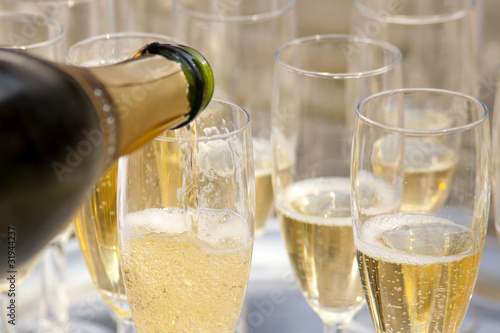 Champaign being pored into glasses. - 31944237