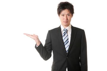 手のひらで案内するスーツの男性