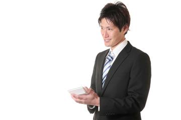 計算機を持っているスーツの男性