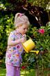 Kind mit Gießkanne beim Blumen giessen