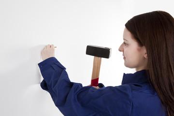 Frau schlägt Nagel in die Wand