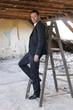 Mann auf der Baustelle steht auf der Leiter