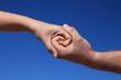 Zwei Personen reichen sich die Hand vor blauem Himmel