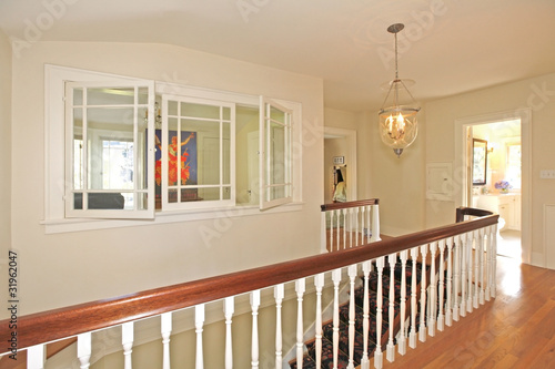 Hallway with staircase and indoor windows