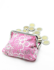 coins spilling out from flower pink money bag or purse isolated