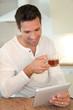 Portrait of man in kitchen drinking tea