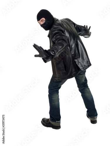 young male thief in balaclava and black leather jacket